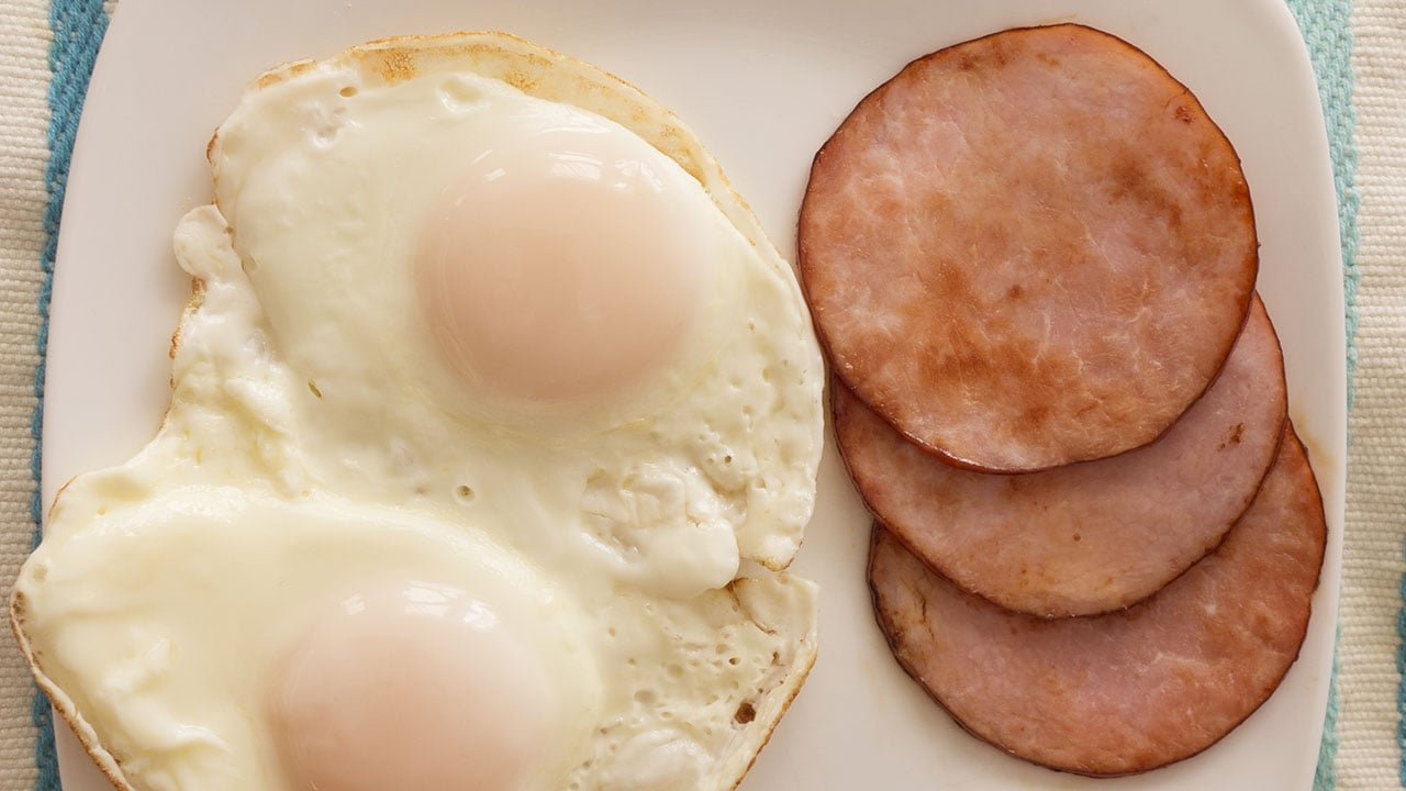A plate of two eggs, over easy and slices of Canadian bacon on a pastel tablecloth.